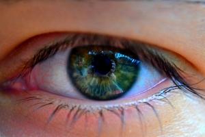Makro fotka chlapeckého oka se zelenou barvou duhovky.
