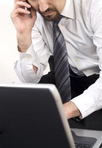 Muž pracující u počítače v nevhodné poloze
