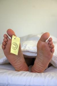 Fotka nohou vykukujících z pod bílé peřiny s papírkem na palci
