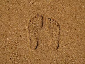 Tisky dvou lidských nohou v morkém písku