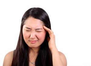 Tmavovlasá žena s bolesí hlavy