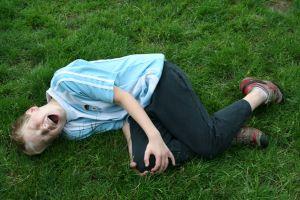 Malý chlapec leží na trávě a drží se v bolestech za nohu