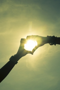 Ruce spojené do tvaru srdce na pozadí se sluncem