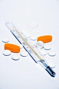 Fotografie injekční stříkačky a lékových tabletek.