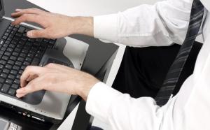 muž, píšící na laptop