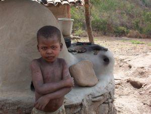 Malé africké dítě, které sedí u hliněné pece