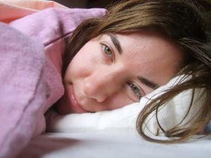 Nemocná dívka leží v posteli.