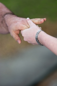 dva lidé se drží za ruce