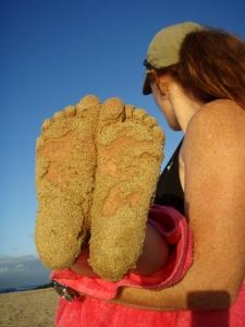 Žena drží dítě, které má plosky nohou od písku