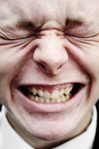 Muž, který  má bolestí skřivenou tvář.