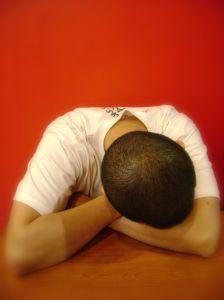 Mladý muž, který usnul únavou u svého pracovního stolu