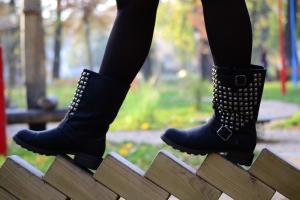 Mladá žena kráčí po dřevěných prknech v černých botách