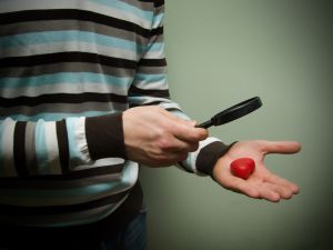 Muž, který stojí a prohlíží si lupou malé rajče