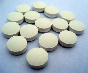 Bílé tabletky poskládané an modrém pozadí