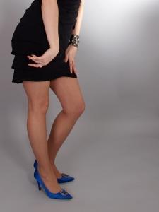 Mladá žena v černých šatech, kteou bolí nohy
