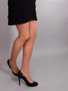 Žena oblečená v černé sukni, silonkách a lodičkách.