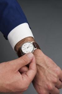 Muž si kontroluje čas na svých hodinkách